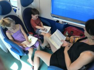 Joy and kids reading books on train